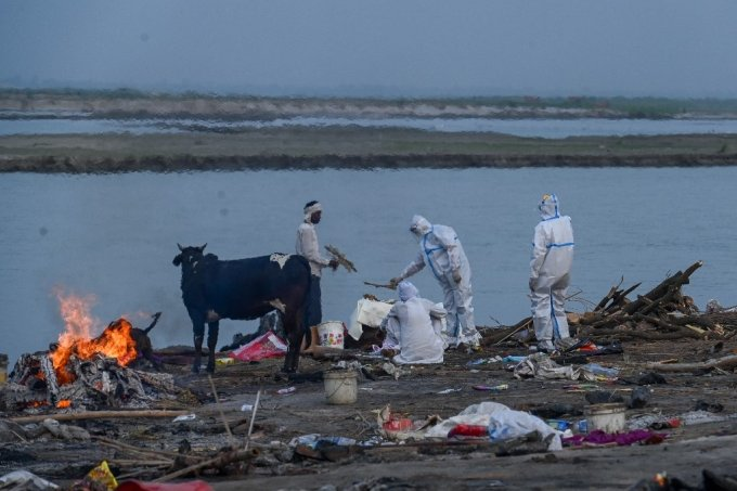 인도 갠지스 강변에서 코로나19 사망자의 가족들이 시신을 화장하기 전 방호복을 입은 채 마지막 의식을 치르고 있다./사진=AFP