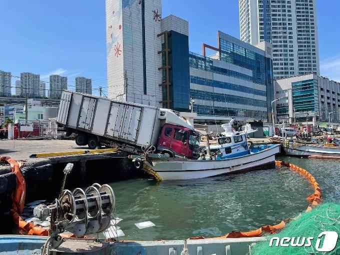 부산 다대항 인근을 지나던 냉동 탑차가 정박 중인 어선위로 추락했다(부산해양경찰서제공)© 뉴스1
