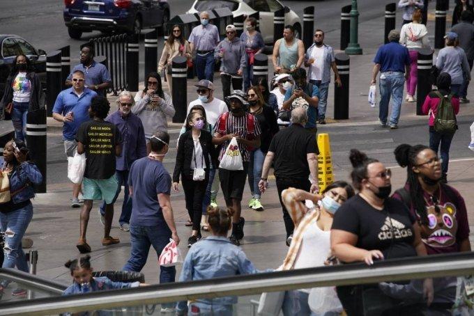[라스베이거스=AP/뉴시스]27일(현지시간) 미 네바다주 라스베이거스에서 마스크를 쓰거나 쓰지 않은 보행자들이 거리를 걷고 있다. 미국 질병통제예방센터(CDC)는 코로나19 백신 접종을 완료한 경우 야외에서 마스크를 쓰지 않아도 된다고 발표하며 야외 마스크 착용에 대한 지침을 완화했다. 2021.04.28.