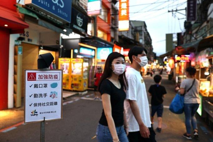 15일 대만 타이베이의 한 야시장에서 시민들이 '마스크를 쓰고 손을 씻고 사회적 거리를 유지하라'는 안내문 앞을 지나고 있다./사진=로이터