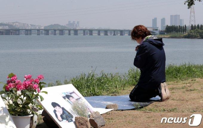 지난 19일 서울 반포한강공원 택시 승강장 인근에 마련된 손씨 추모 공간을 찾은 한 시민이 무릎을 꿇은 채 기도하고 있다/사진제공=뉴스1