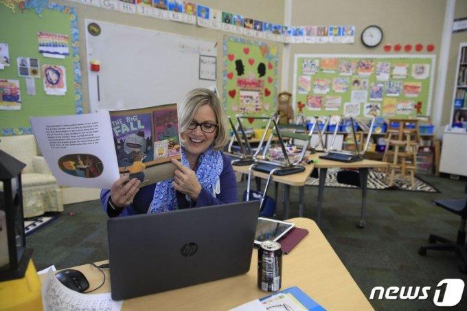 (AFP=뉴스1) 이동원 기자 = 15일(현지시간) 켄터키 주 세인트 프랜시스 스쿨의 2학년 빈 교실에서 조앤 콜린스 브록 교사가 온라인으로 학생들을 가르치고 있다. 브록은 신종 코로나바이러스 감염증(코로나19) 대유행으로 켄터키 주의 학교가 문을 닫자 학생들에게 매일 온라인으로 수업을 하고 있다.  (C) AFP=뉴스1