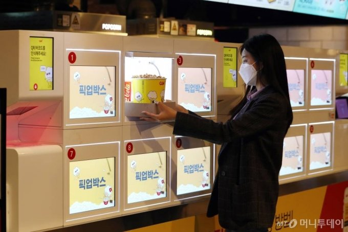 CJ CGV가 대면 서비스를 최소화한 '언택트시네마'를 선보인 가운데 21일 서울 CGV 여의도에서 한 시민이 직원과 대면 없는 '픽업박스'를 이용해 팝콘을 구매하고 있다. '언택트시네마'는 다양한 하이테크 기술을 통해 언택트(Un-tact) 서비스를 기반으로 새롭고 간편하게 극장 시설을 이용할 수 있는 서비스다. /사진=이기범 기자 leekb@