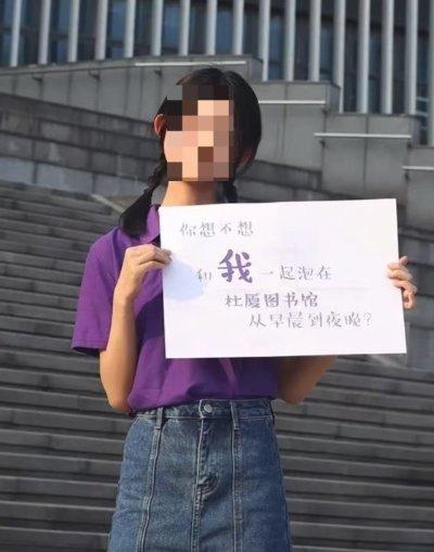 중국 난징대의 한 여학생이 '나랑 온종일 도서관에 같아 있을래?'라는 문구의팻말을 들고 있다. /사진=웨이보 캡처
