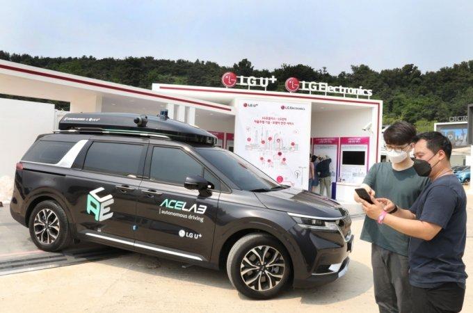 LG유플러스 관계자들이 전시부스에서 자율주행차를 살펴보고 있는 모습.