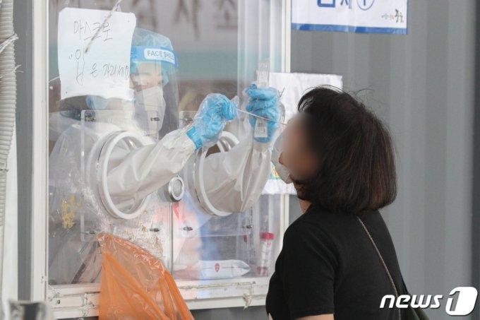 (서울=뉴스1) 성동훈 기자 = 10일 오전 서울역 광장에 마련된 중구 임시선별진료소에서 의료진이 코로나19 검사를 하고 있다. 이날 0시 기준 신종 코로나바이러스 감염증(코로나19) 신규 확진자는 611명으로 연이틀 600명대를 기록했다. 2021.6.9/뉴스1