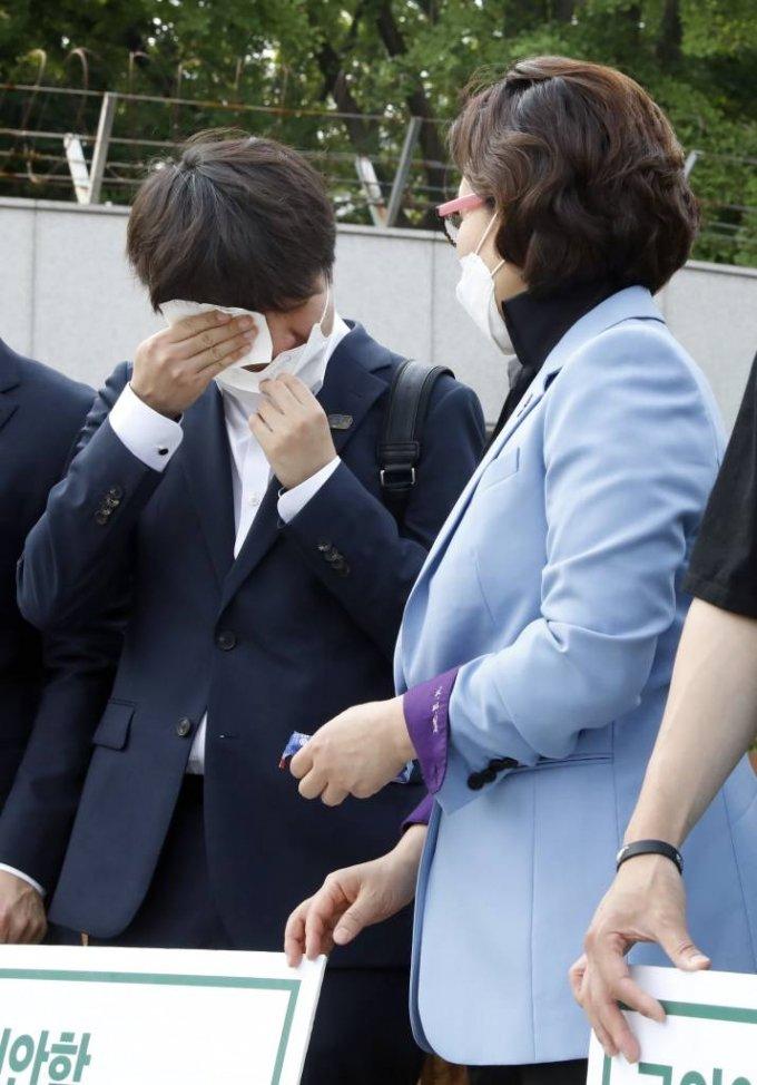 국민의힘 이준석 당대표가 후보 시절인 이달 9일 서울 국방부 앞에서 피켓시위중인 천안함재단, 유가족회, 생존자전우회원들을 찾아 함께 피켓을 들고 있던 중 눈물을 닦고 있다. / 사진제공=뉴시스