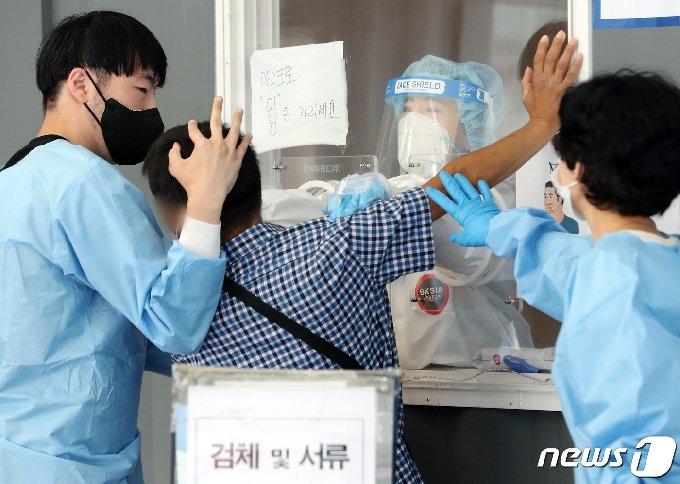 11일 오전 서울역 광장에 마련된 중구 임시선별진료소에서 의료진들이 한 취객의 코로나19 검사를 위해 힘쓰고 있다. 2021.6.11/뉴스1 © News1 이동해 기자