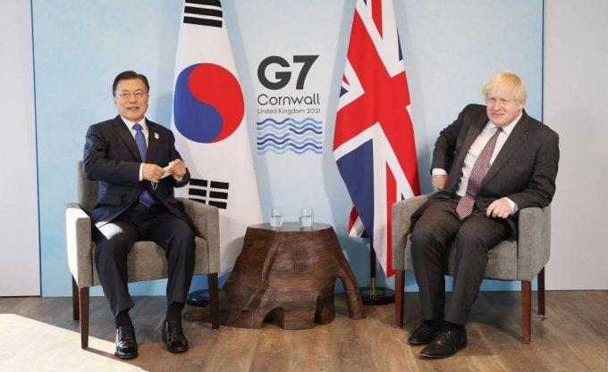 [콘월(영국)=뉴시스]박영태 기자 = G7 정상회의 참석차 영국을 방문 중인 문재인 대통령이 13일(현지시간) 영국 콘월 카비스베이 양자회담장에서 보리스 존슨 영국 총리와 한-영 정상회담을 하기 위해 마스크를 벗고 있다. 2021.06.13. since1999@newsis.com