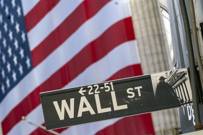 FILE - In this Monday, Sept. 21, 2020, file photo, a Wall Street street sign is framed by a giant American flag hanging on the New York Stock Exchange in New York. Stocks are falling in early trading on Wall Street Monday, Oct. 26, 2020, and deepening last week's losses. (AP Photo/Mary Altaffer, File)