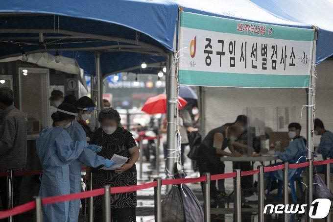 18일 오전 서울 중구 서울역광장에 마련된 신종 코로나바이러스 감염증(코로나19) 임시 선별검사소를 찾은 시민들이 안내를 받고 있다. 2021.6.18 /뉴스1 © News1 이승배 기자