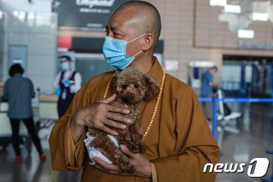 지 시앙(51)은 보살피던 유기견을 미국 시애틀로 입양 보내기 위해 상하이 국제공항에 도착했다. /사진제공= AFP/뉴스1