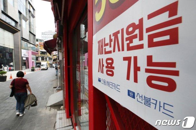 더불어민주당이 재난지원금 전 국민 지급 원칙을 재확인한 22일 오전 서울 중구 명동의 한 점포에 재난지원금 사용 가능함을 알리는 안내문이 부착돼 있다.  /사진=뉴스1
