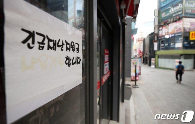 22일 오전 서울 중구 명동의 한 점포에 재난지원금 사용 가능함을 알리는 안내문 옆으로 한산한 거리가 보이고 있다. /사진=뉴스1