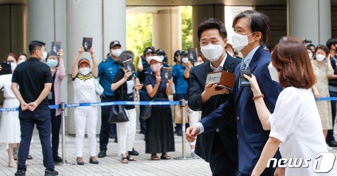 조국 전 법무부 장관이 25일 서울 서초구 중앙지방법원에서 열린 공판에 출석하자 지지자들이 조 전 장관이 쓴 회고록 '조국의 시간'을 든채 응원하고 있다.  2021.6.25/뉴스1 © News1 안은나 기자