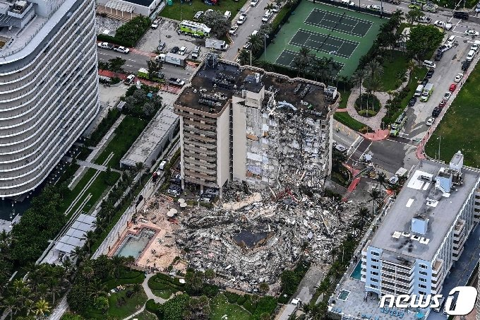 24일(현지시간) 플로리다주 마이애미의 서프사이드에 있는 12층 짜리 챔플레인 타워 콘도 건물이 폭격 맞은 듯 무너져 1명이 사망하고 99명이 실종된 현장의 모습이 보이고 있다. 현재 붕괴 원인은 찾지 못했으며 플로리다 주지사는 피해를 입은 가족들을 돕기 위해 비상사태를 선포했다. © AFP=뉴스1
