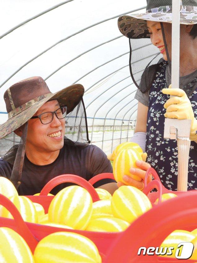김경목·박귀옥씨 부부가 참외를 수확하며 활짝 웃고 있다. 2021.6.26 /© 뉴스1
