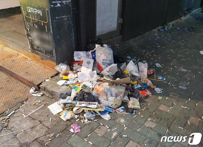 '영업시간 제한 해제' 및 '9인 이상 사적모임 금지'가 시행된 첫 주말인 26일 부산 부산진구 서면 거리 구석에 담배꽁초와 각종 쓰레기가 쌓여있다© 뉴스1
