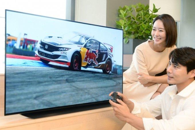 LG전자 모델이 48인치 올레드 TV로 게임을 즐기고 있다. /LG전자 제공