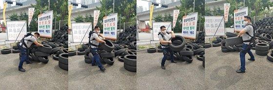 기자가 웨어러블 로봇 '스텝업'을 착용하고 타이어를 옮기는 작업을 하는 모습/사진=류준영
