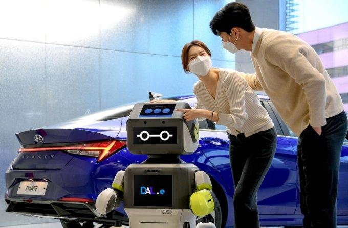 현대차 송파대로지점을 찾은 고객이 인공지능 로봇 '달이'를 체험하고 있다. /사진제공=현대차