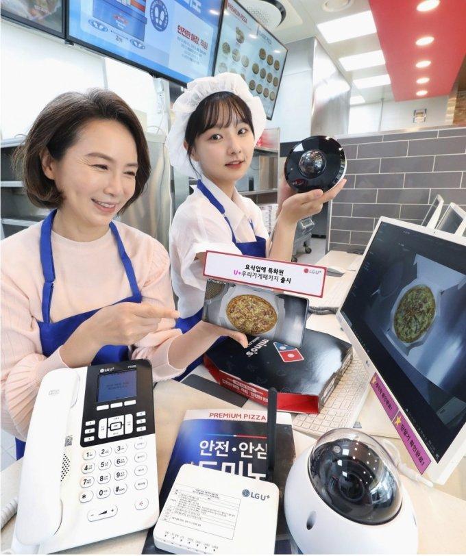 LG유플러스는 요식업 특화 소상공인 대상 패키지인 'U+우리가게패키지'를 새롭게 출시했다고 13일 밝혔다. 사진은 LG유플러스 모델이 도미노피자에 설치된 매장안심형 CCTV를 통해 피자 조리 과정을 모니터링하는 모습. /사진=LG유플러스