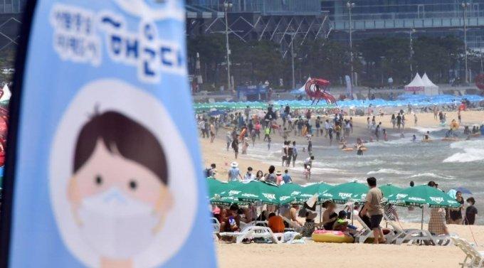 지난 11일 해운대해수욕장을 찾은 시민과 관광객들이 물놀이를 즐기고 있는 가운데 백사장에 마스크 착용을 알리는 깃발이 설치돼 있다. /사진=뉴시스