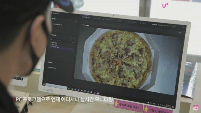 도미노피자 매장에서 '매장안심형 CCTV'로 피자 제조 상황을 모니터링 하는 모습. /사진=LG유플러스
