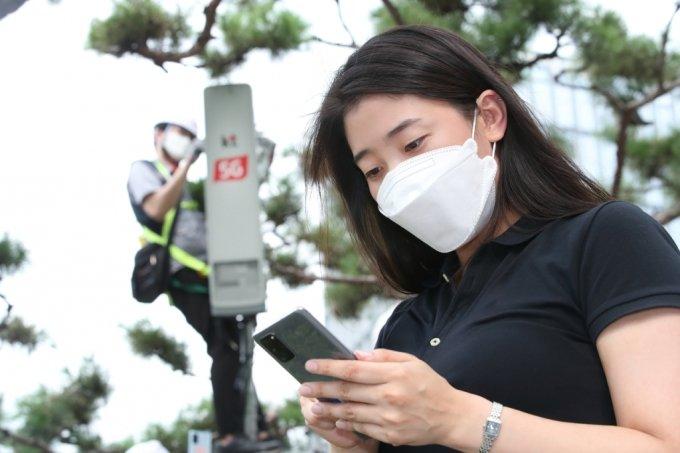 KT 직원이 5G SA를 적용한 갤럭시S20을 이용하고 있다. /사진=KT