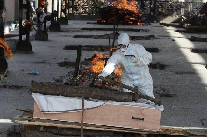 지난 4월23일(현지시간) 인도 카슈미르주 잠무의 화장터에서 코로나19로 숨진 사람의 장례식이 진행되는가운데 방호복을 입은 가족이 마지막 인사를 하고 있다. /AP=뉴시스