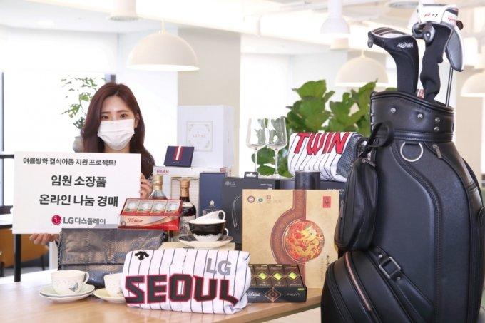LG디스플레이 임원들이 기부한 경매 물품들을 직원이 소개하고 있다. /사진제공=LG디스플레이