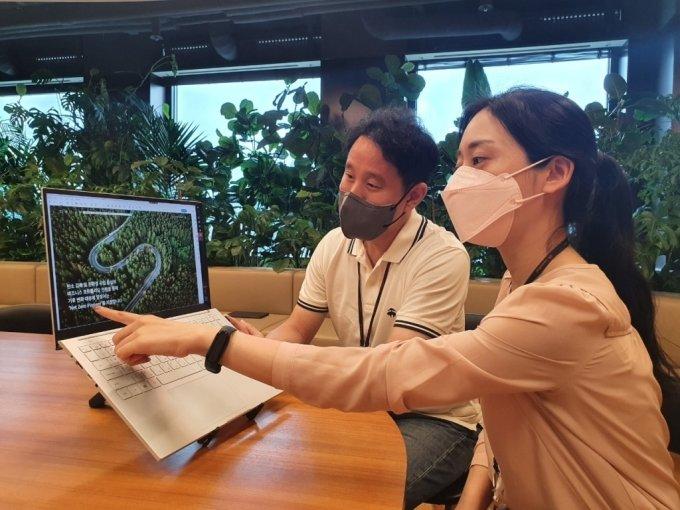 SK이노베이션 구성원들이 서울 종로구 SK서린빌딩에서 넷제로 특별 보고서를 살펴보고 있다./사진=SK이노베이션