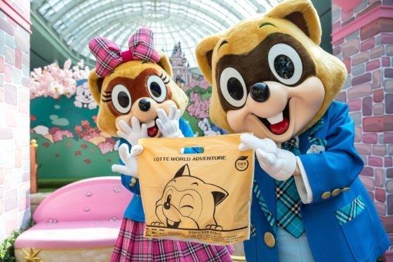 롯데월드 대표 캐릭터 로티와 로리가 친환경 생분해성 쇼핑 봉투를 들고 있다. /사진=롯데월드