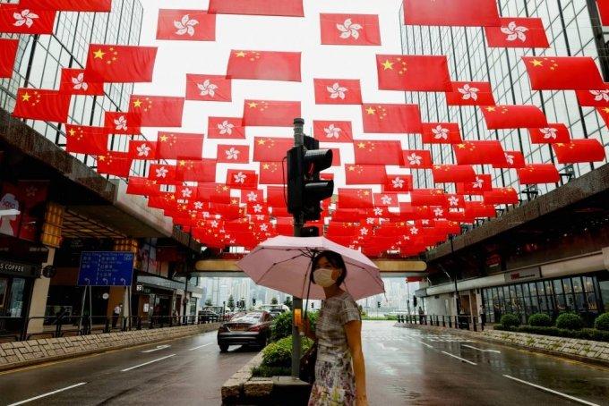중국 홍콩에서 한 여성이 중국 공산당 창당 100주년을 앞두고 쇼핑몰 밖에 걸려 있는 중국과 홍콩의 국기 아래를 걷고 있다. 2021.06.28 /사진=로이터통신