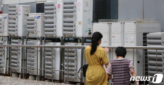 (대전=뉴스1) 김기태 기자 = 폭염으로 전력 수요가 급증하고 있는 가운데 20일 오후 대전 중구에 위치한 걸물 외벽에 설치된 에어컨 실외기 앞으로 시민이 지나고 있다. 2021.7.20/뉴스1