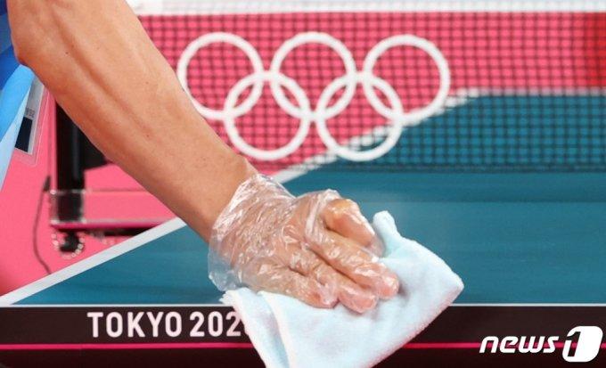 (도쿄=뉴스1) 송원영 기자 = 2020 도쿄 올림픽을 3일 앞둔 20일 일본 도쿄체육관에서 올림픽 관계자가 신종 코로나바이러스 감염증(코로나19) 확산 방지를 위해 탁구대를 소독하고 있다.  2021.7.20/뉴스1