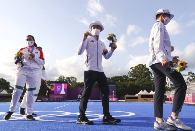 대한민국 양궁 대표팀 안산과 김제덕이 24일 오후 일본 도쿄 유메노시마 양궁장에서 열린 2020 도쿄올림픽 양궁 남녀혼성단체전에서 우승을 차지한 뒤 금메달을 들고 기뻐하고 있다. / 사진제공=뉴시스