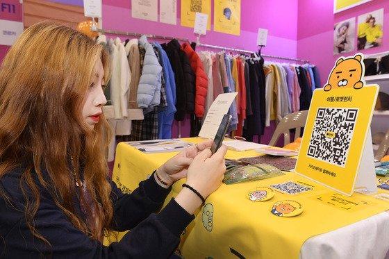 서울 중구 동대문 디자인플라자에서 열린 '슈퍼! 마켓페스트 2018' 에서 한 참석자가 현금 없이 스마트폰만 있으면 오프라인에서 간편하게 결제할 수 있는 카카오페이로 상품을 구매하고 있다./사진=카카오페이