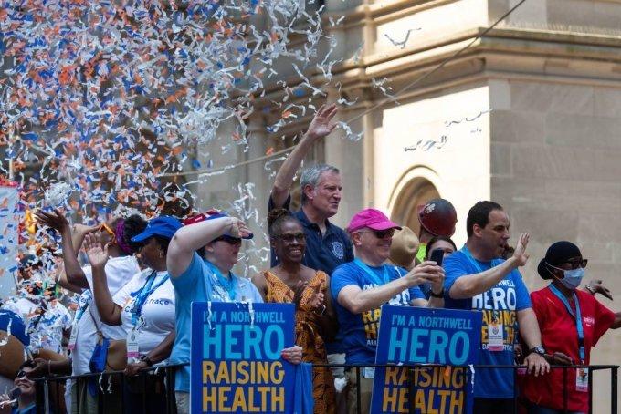 [뉴욕=신화/뉴시스] 빌 드 블라시오(가운데) 뉴욕 시장 7일(현지시간) 미국 뉴욕에서 시민들과 함께 색종이 테이프 행렬에 참여해 손을 흔들며 인사하고 있다. 이날 뉴욕시의 필수 근로자 수백 명이 코로나19로부터의 회복을 알리는 색종이 테이프 행렬에 참여했다. 이 행사는 코로나19 대유행 중에 일선에서 싸워야 했던 의료진, 응급구조대원, 교육 및 보육 종사자, 운송 근로자, 비상식량 공급 업체, 통신 및 배달 사업자 등 필수 근무자들을 기리기 위해 열렸다. 2021.07.08.
