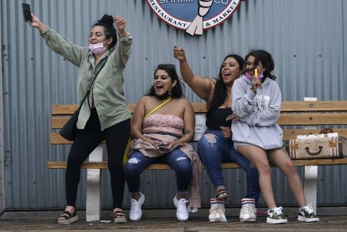 5월 13일(현지시간) 미국 캘리포니아주 샌타모니카에서 마스크를 쓰지 않은 방문객들이 도착한 친구를 반기고 있다. 이날 질병통제예방센터(CDC)는 백신 접종자가 대부분의 경우 마스크를 쓰지 않아도 된다고 발표했다. 2021.05.14./AP=뉴시스