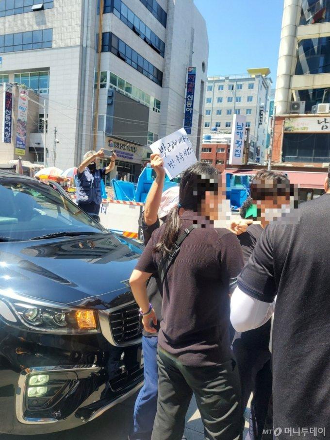 """한 40대 여성이 자갈치 시장 입구에서 """"박근혜 전 대통령을 왜? 구속시켰나""""라고 적힌 손팻말을 들고 윤 전 총장에게 항의하고 있다./사진=안채원 기자"""