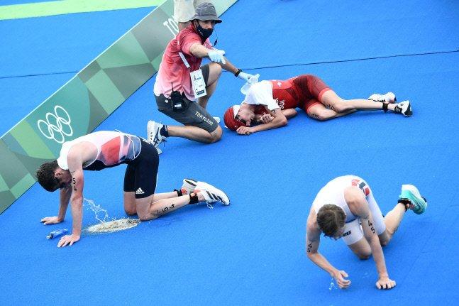 26일 일본 도쿄 오다이바 해상공원에서 열린 남자 트라이애슬론 결승전을 마친 선수들이 결승선을 통과하자마자 땅에 쓰러져 구토를 하는 등 고통을 호소하고 있다. /사진=AFP