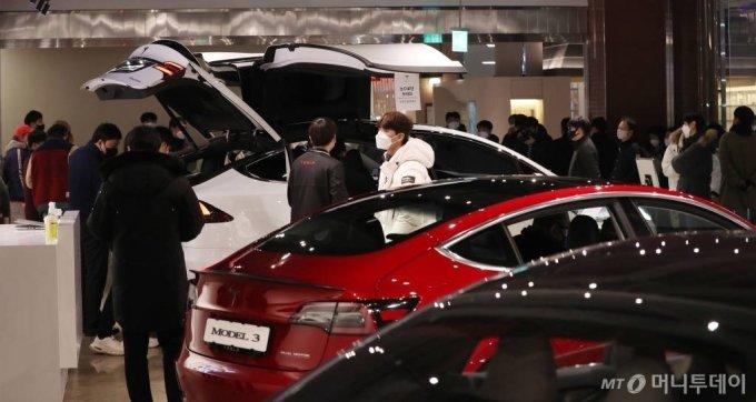 테슬라 코리아가 13일 서울 영등포구 롯데백화점 영등포점에서 '모델 Y'를 국내 최초공개한 가운데 시민들이 차량을 살펴보고 있다. /사진=김휘선 기자 hwijpg@