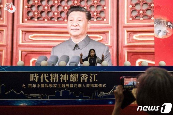 (홍콩 AFP=뉴스1) 우동명 기자 = 8일(현지시간) 홍콩 컨벤션센터에서 열린 중국 공산당 창당 100주년을 기념하는 전시회서 방문객이 시진핑 국가 주석의 스크린 앞에서 포즈를 취하고 있다.  (C) AFP=뉴스1