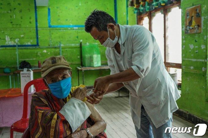 20일(현지시간) 부탄의 수도 팀부에 마련된 코로나19 백신 접종 센터에서 노인이 백신을 맞고 있다.  /AFP=뉴스1