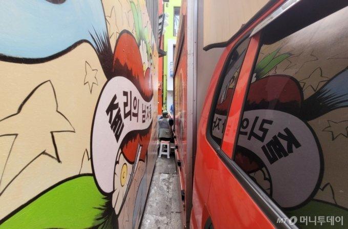 29일 서울 종로구 관철동의 한 중고서점에 그려진 '쥴리의 벽화'가 자동차로 가려져 있다. 성인은 두 팔을 최대한 움츠리고 들어가도 진입이 어렵다. / 사진 = 오진영 기자