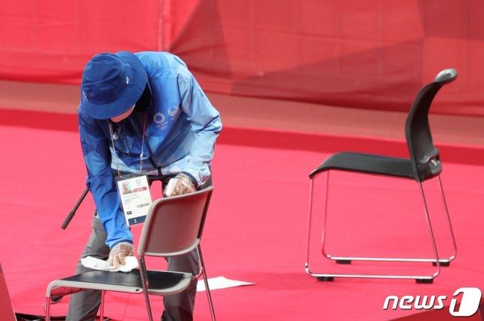 (도쿄=뉴스1) 이재명 기자 = 28일 오후 일본 도쿄 무사시노노모리 종합 스포츠플라자에서 열린  '2020 도쿄올림픽' 배드민턴 경기를 앞두고 자원봉사자들이 심판진이 머물 자리를 소독하고 있다. 2021.7.28/뉴스1