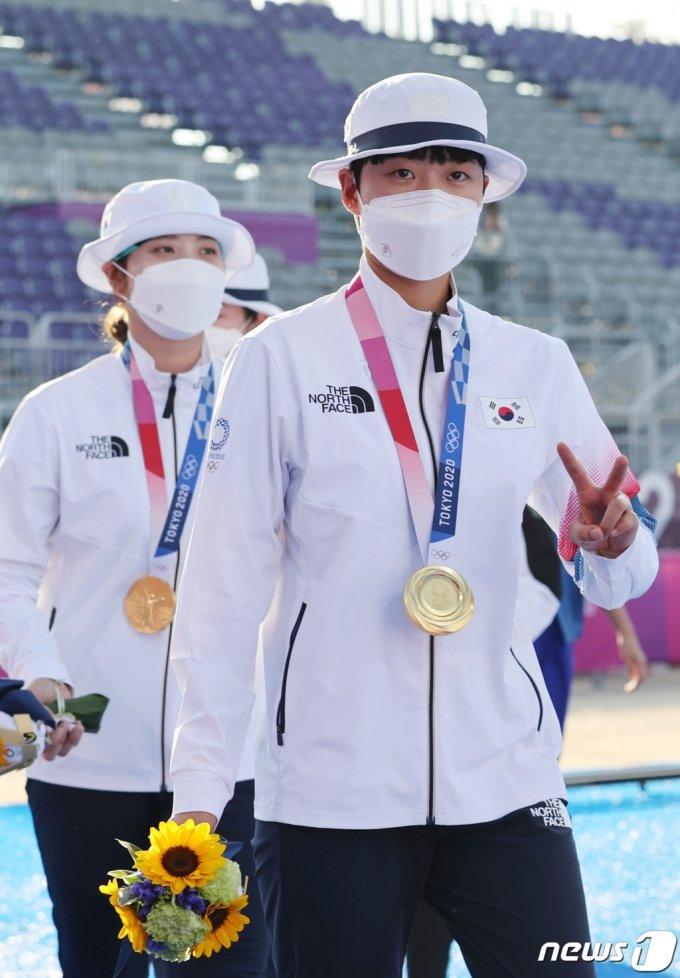 양궁 안산이 25일 일본 도쿄 유메노시마 공원 양궁장에서 열린 2020 도쿄올림픽 양궁 여자단체전 시상식에서 금메달을 목에 걸고 '브이'를 표시하고 있다.  한국 여자 양궁팀은 올림픽 단체전 9연패라는 대기록을 세웠다 /사진=뉴스1