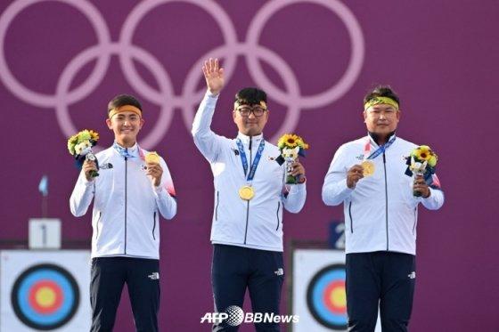 한국 남자 양궁 대표팀의 김제덕(왼쪽부터)-김우진-오진혁이 단체전 금메달을 목에 건 채 인사하고 있다. /AFPBBNews=뉴스1