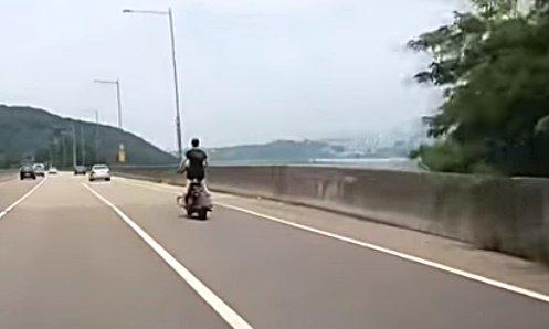 한 운전자가 도로에서 일어선 채 오토바이를 타는 모습을 발견했다며 지난달 13일 제보한 영상./사진=유튜브 채널 '한문철Live'